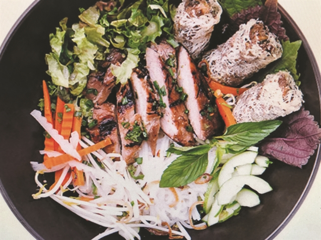 FOOD HEAVEN: Rice noodle salad with grilled pork, prawn spring rolls and sweet and sour fish sauce is among the Vietnamese favourites added to L'Usine menu by head chef Nicholas de Gersigny. VNS photo Minh Phi