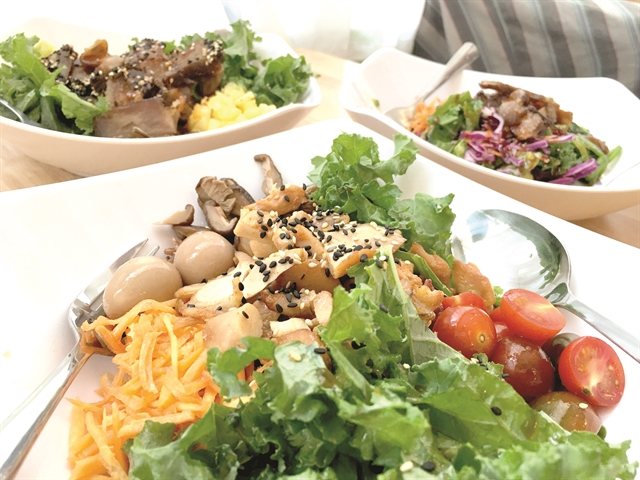 A combination of starter, main dish and dessert with corn, brown rice, salad, eggs, kale, cucumber, tomatoes and cabbage with honey mustard chicken and teriyaki sauce. Photo Hồ Hoàng