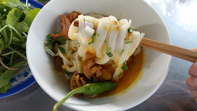 Mỳ Quảng noodles with chicken at a restaurant in central Việt Nam.  Phú Chiêm Village is known as the original home of the spicy dish, and villagers continue to make noodles by hand for restaurants and street vendors in nearby cities. VNS Photo Công Thành